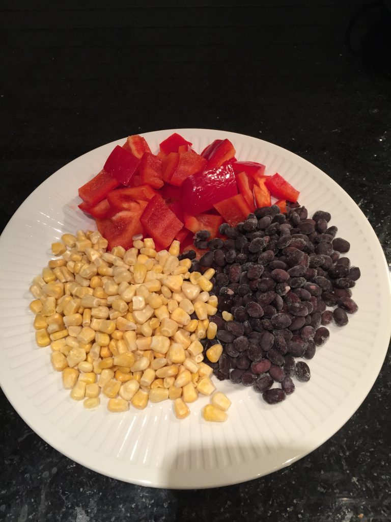 Chop your bell peppers and set aside the frozen beans and corn to make the BBQ chicken burrito bowls
