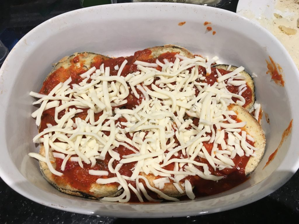 layer tomato sauce and mozzarella cheese on top of the eggplant rounds